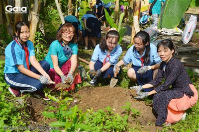 Giám đốc Gaia, Phó Hiệu trưởng trường An Phú và các em học sinh đang cùng nhau lấp đất cho cây.