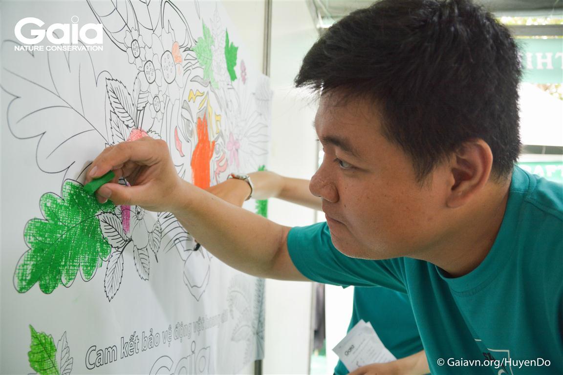 Luân, Cán bộ giáo dục môi trường Trung tâm Bảo tồn thiên nhiên Gaia đang tô màu tranh Hổ cùng mọi người.