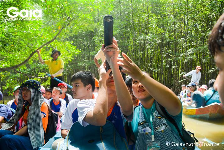 Tình nguyện viên Gaia hướng dẫn học sinh sử dụng ống nhòm quan sát Dơi nghệ.